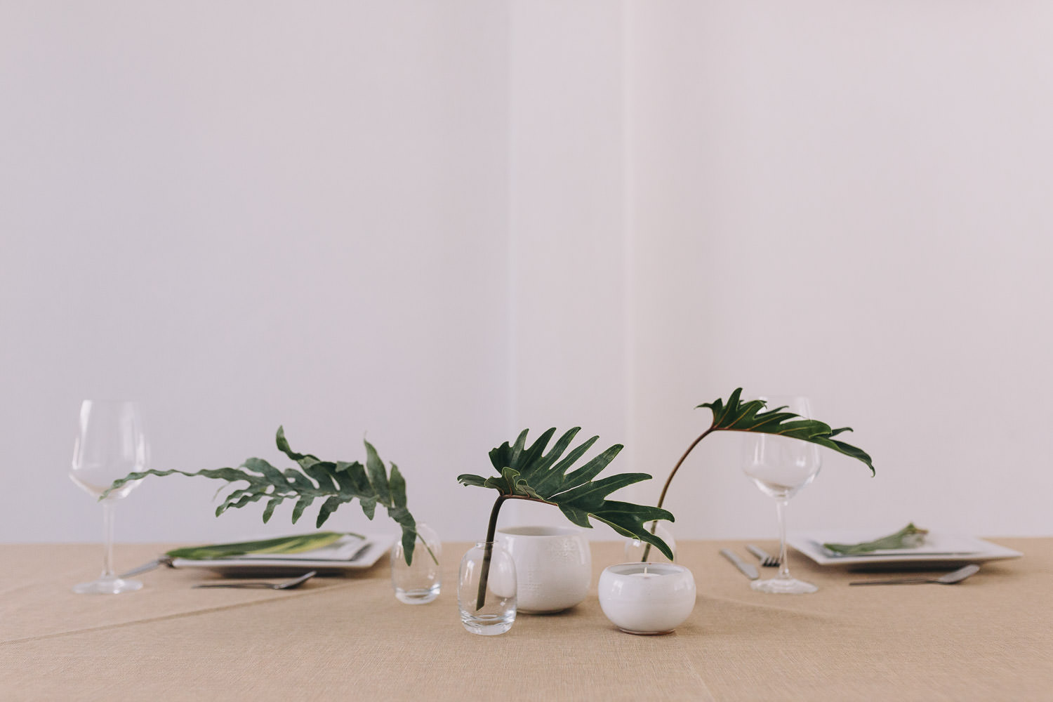 Tropical foliage in simple vases as a table decoration for a wedding