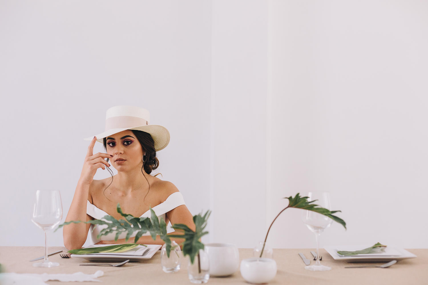 Boho bride with a hat sitting at a simple banquet table