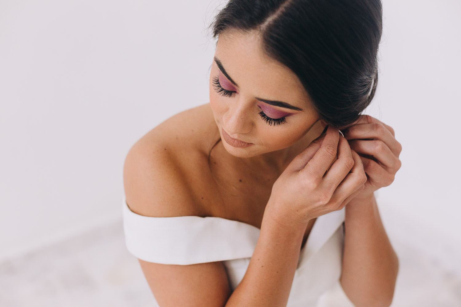 Mexican bride putting on earrings on her wedding day