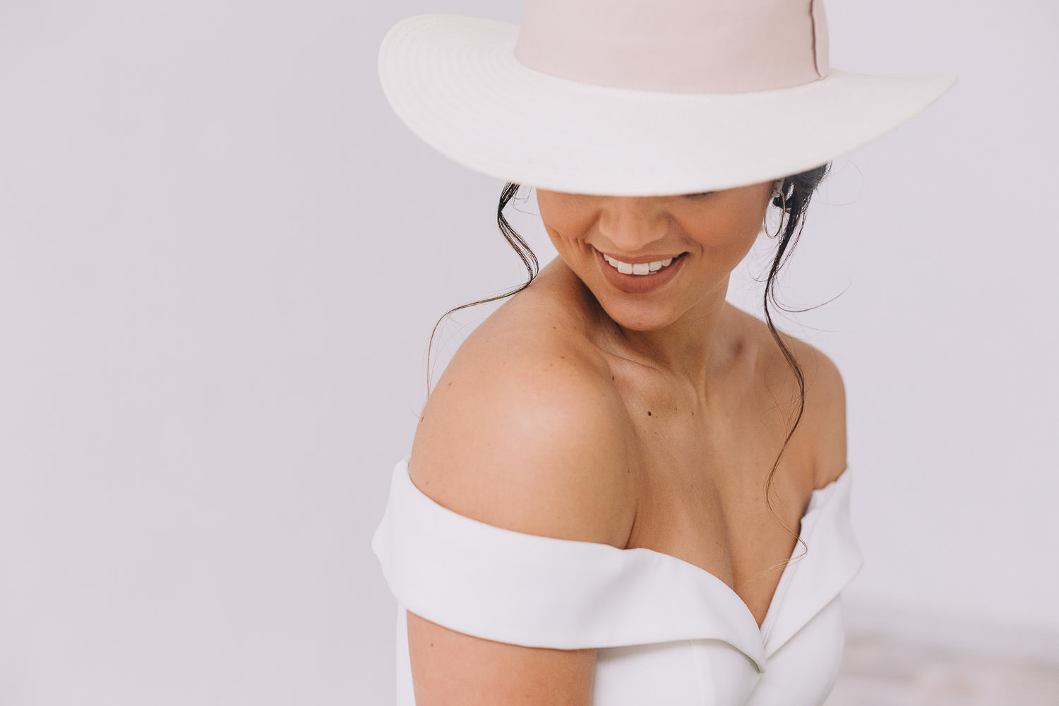 Boho bride with a hat and shoulder less wedding dress smiling