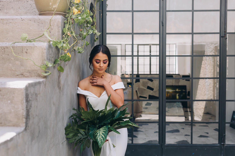 Bride leaning unto a wall in an urban wedding location in Mexico, minimalist wedding Mexico
