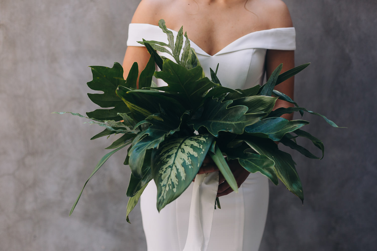 Bride holding a bouquet of green foliage in front of a dark wall